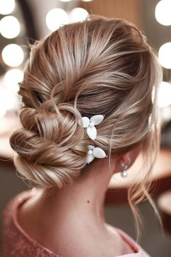 bridesmaid hairstyles curly low bun with flower pins xenia_stylist