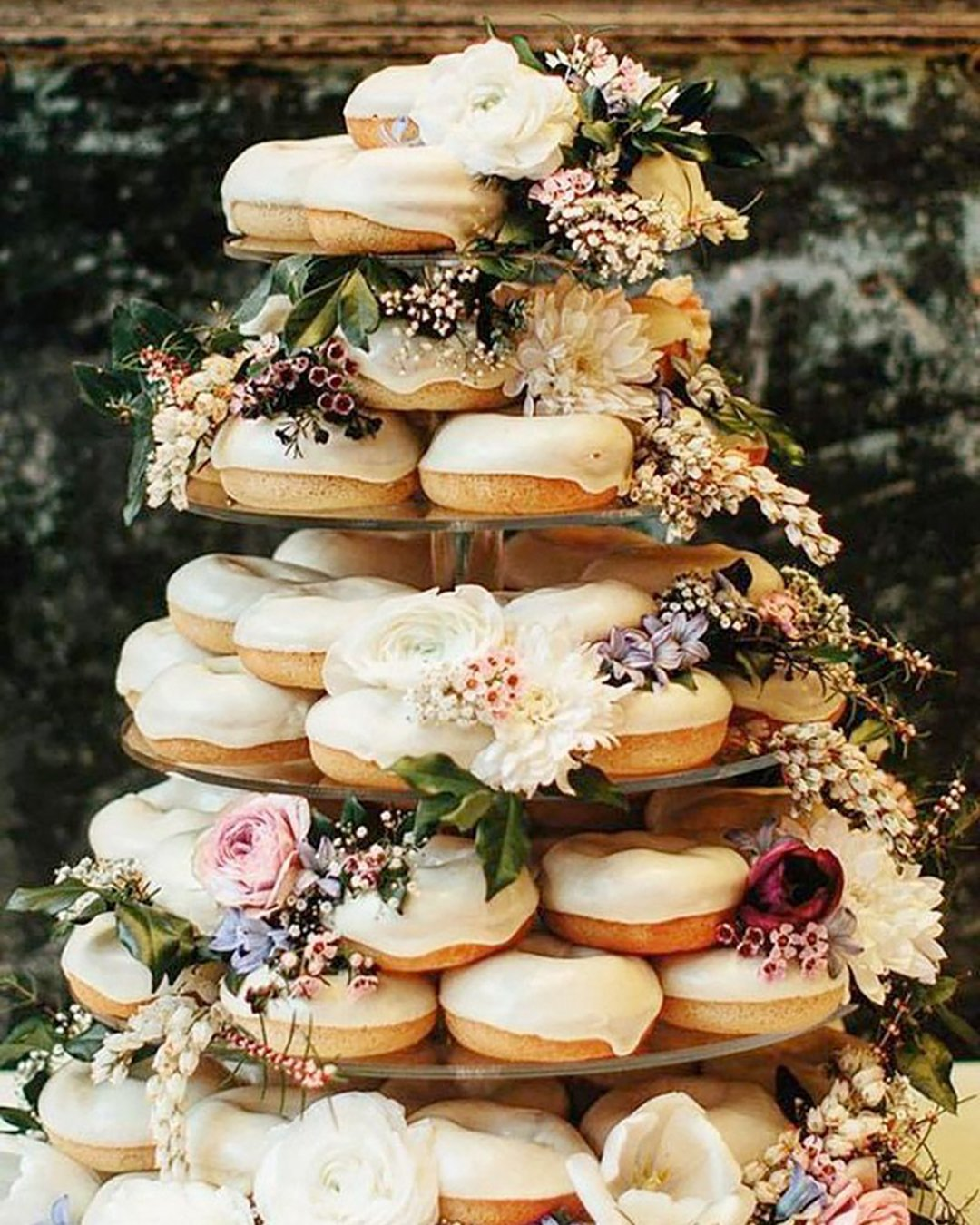 non traditional wedding dessert ideas white donuts tower with roses dahlias greenery paulbamford