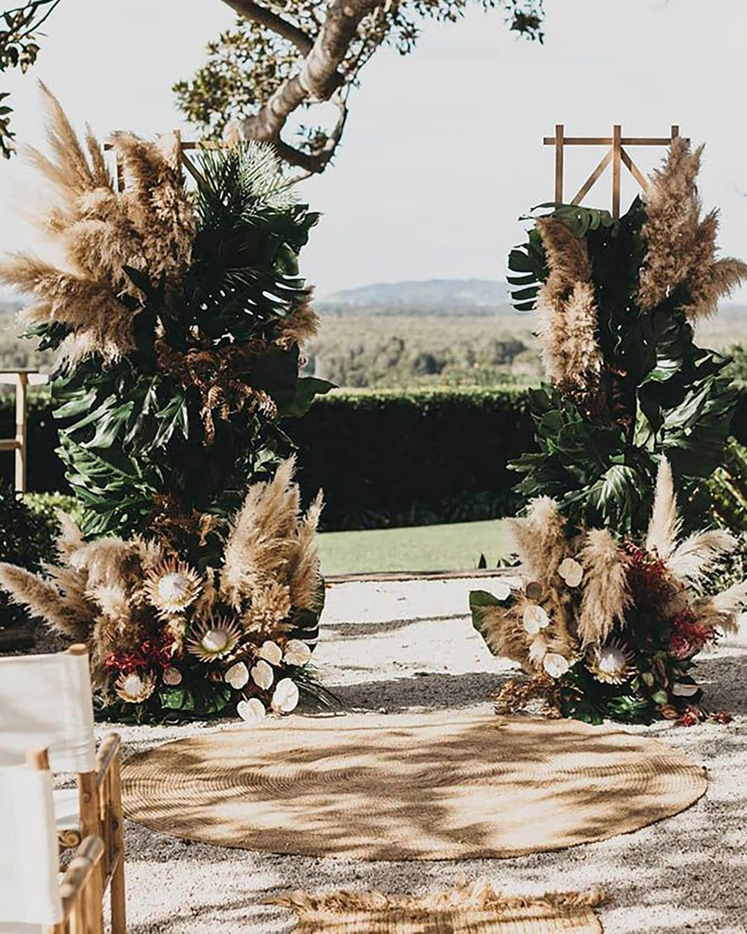 cheap boho decor arch with big tropical leaves and pampas grass shaneshepherdweddings